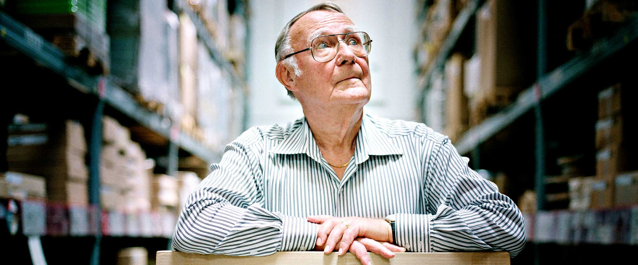 A portrait of a young Ingvar Kamprad posing next to the IKEA store in Älmhult.
